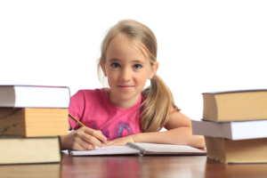 Little schoolgirl behind the books writing her homework (isolated on white background)